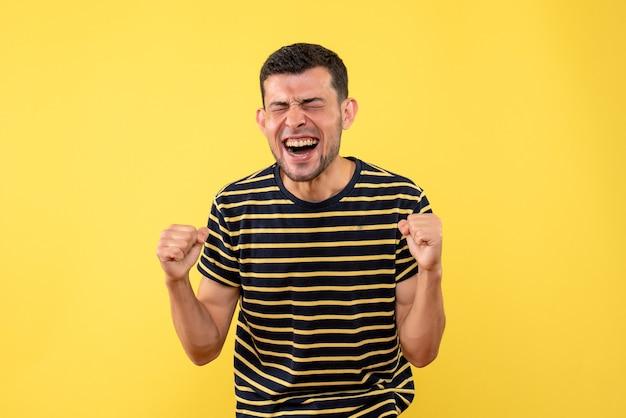 Vista frontal exultante homem bonito em uma camiseta listrada em preto e branco, mostrando o gesto vencedor em um fundo amarelo isolado