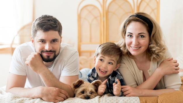 Vista frontal família feliz e seu cachorro fofo