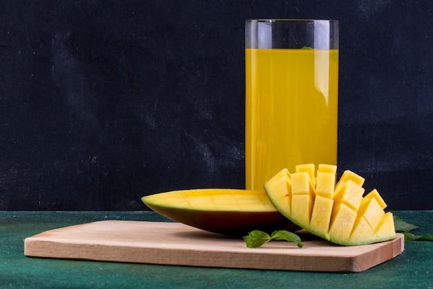 Vista frontal fatiada manga no quadro-negro com um copo de suco de laranja e folhas de hortelã