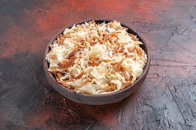 Vista frontal fatiada massa cozida com arroz em prato de superfície escura farinha de massa