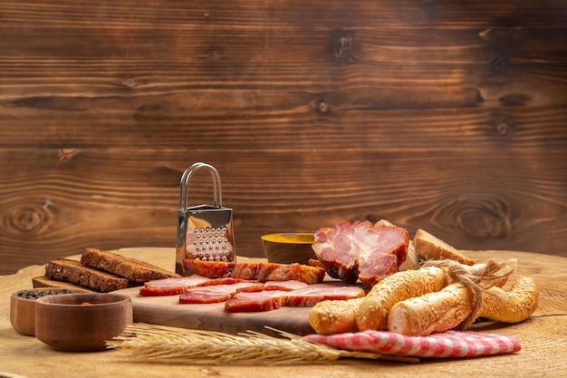Vista frontal fatias de becon em temperos de tábua de cortar em pequenas tigelas ralador de pão marrom e branco na mesa de madeira