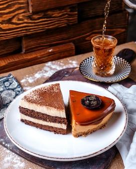Vista frontal fatias de bolo pedaços de bolo de chocolate dentro de chapa branca, juntamente com chá quente no chão marrom