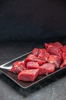 Vista frontal fatias de carne fresca dentro de prato preto longo em fundo escuro refeição jantar carne animal açougueiro salada churrasco comida