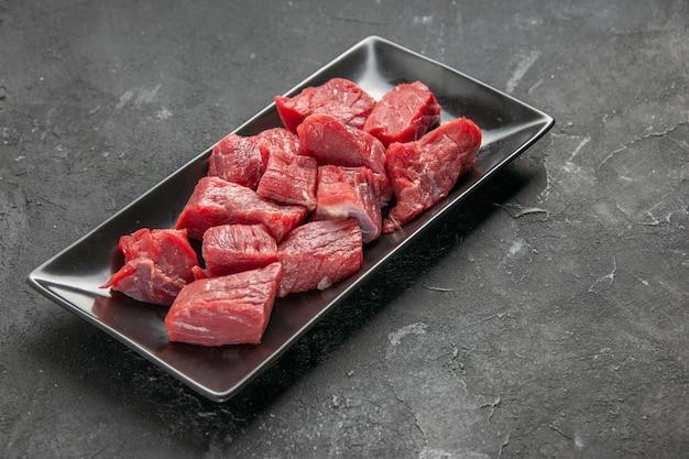 Vista frontal fatias de carne fresca dentro de prato preto longo em fundo escuro refeição jantar carne animal salada churrasco comida açougueiro