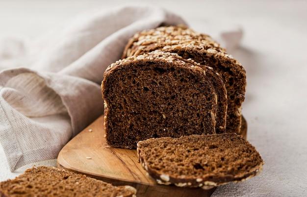 Vista frontal fatias de pão com grãos na placa de madeira