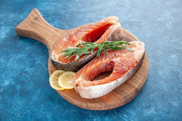 Vista frontal fatias de peixe cru com rodelas de limão no churrasco azul