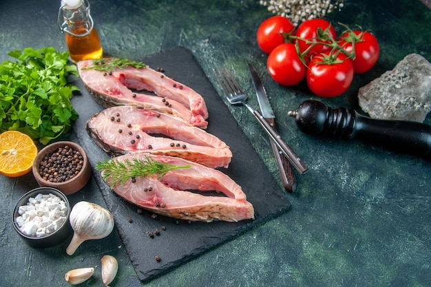 Vista frontal fatias de peixe fresco com verdes e tomates na superfície azul escuro frutos do mar salada refeição oceano jantar cor carne crua água fotos