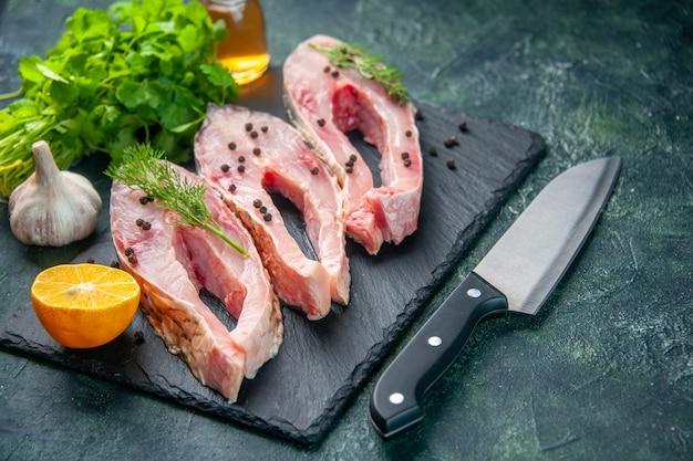 Vista frontal fatias de peixe fresco com verdes na superfície azul-escuro refeição carne do oceano cor crua jantar água frutos do mar foto
