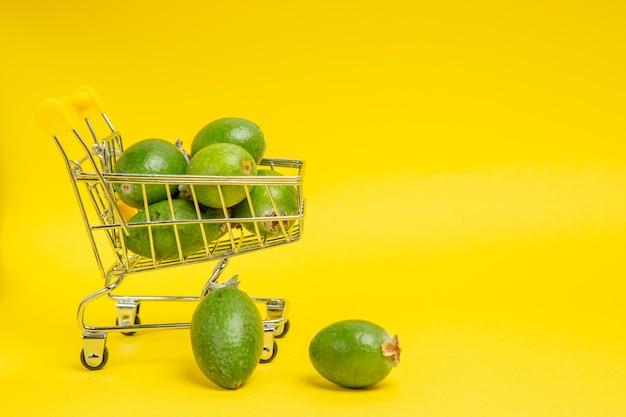 Vista frontal feijoa verde fresca dentro de uma pequena cesta móvel na superfície amarela com fruta suave exótica