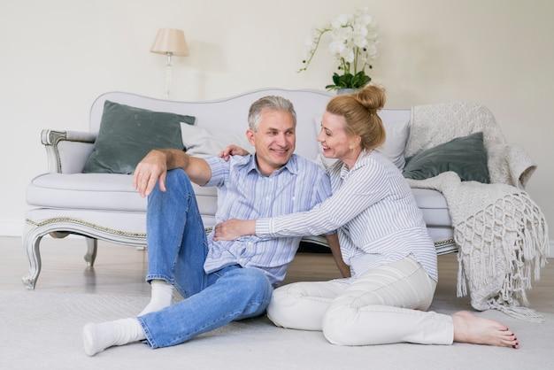 Vista frontal feliz casal sênior juntos no chão