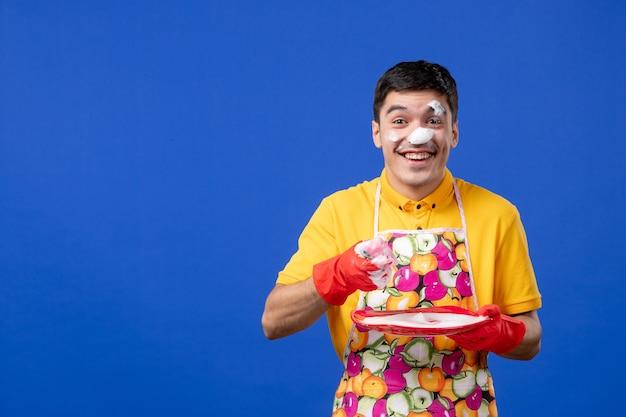 Vista frontal feliz dona de casa com espuma no prato de lavagem de rosto no espaço azul