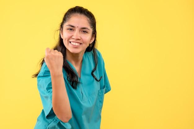 Vista frontal feliz médica de uniforme, mostrando gesto vencedor em fundo amarelo isolado