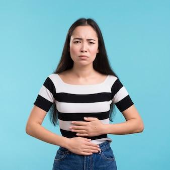 Vista frontal feminina com dor de estômago