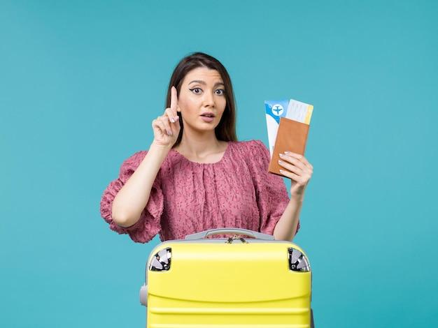 Vista frontal feminina em férias segurando sua carteira e ingressos em fundo azul claro viagem férias viagem mulher verão mar
