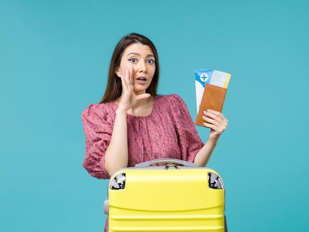 Vista frontal feminina em férias segurando sua carteira e ingressos em fundo azul, viagem, viagem, mulher, verão