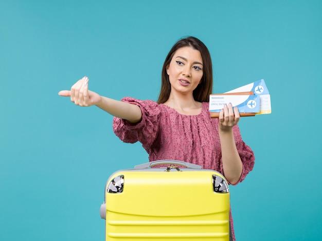 Vista frontal feminina em férias segurando sua carteira e ingressos na viagem de fundo azul mulher viagem de verão férias no mar