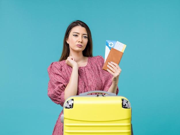 Vista frontal feminina em férias segurando sua carteira e ingressos no fundo azul viagem férias viagem mulher verão mar