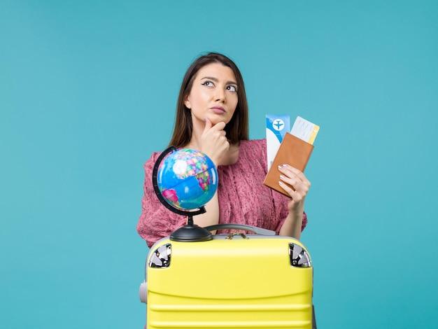 Vista frontal feminina em viagem segurando carteira com ingressos e pensando no fundo azul mar mulher viagem viagem de férias viagem