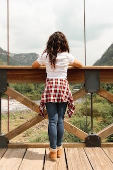 Vista frontal feminina na ponte admirando a natureza