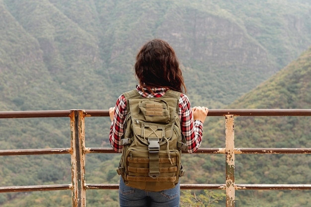 Vista frontal feminina na ponte, olhando a natureza