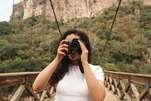 Vista frontal feminina na ponte tirando fotos