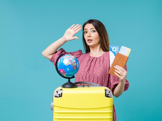 Vista frontal feminino em viagem segurando carteira com ingressos no fundo azul mar viagem mulher viagem viagem de férias