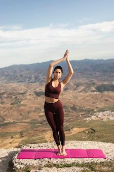 Vista frontal feminino praticando ioga