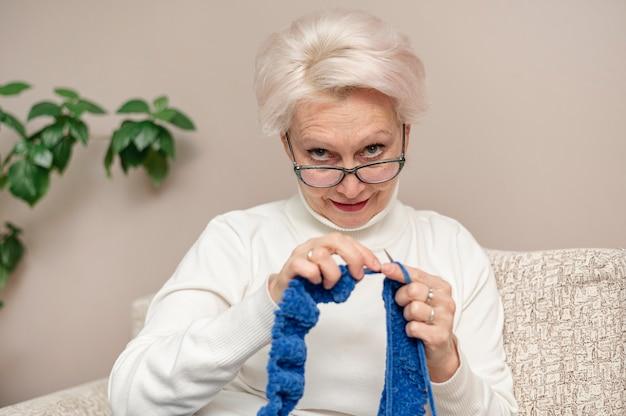 Vista frontal feminino sênior com óculos de tricô