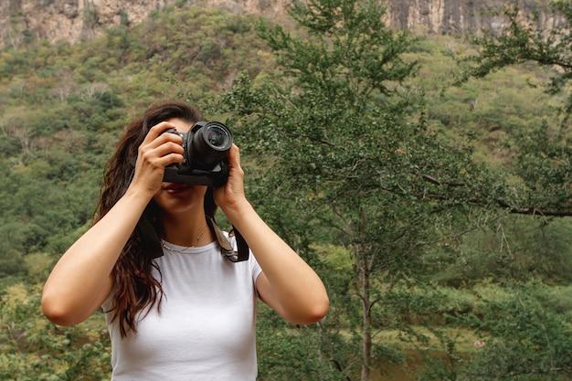 Vista frontal feminino viajante tirando fotos