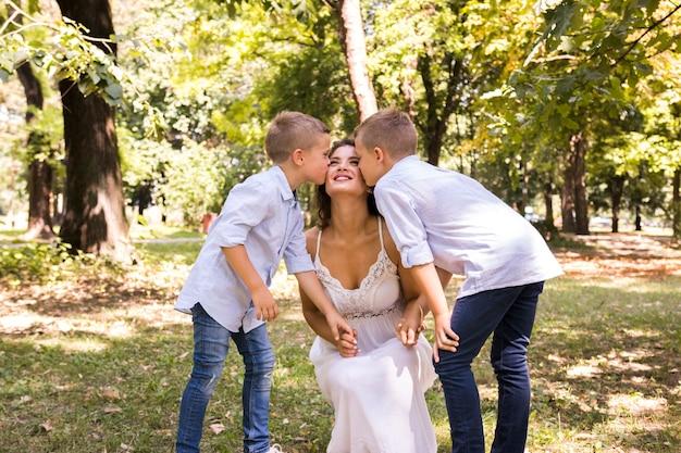 Vista frontal filhos beijando sua mãe