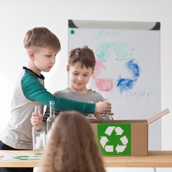 Vista frontal filhos bonitos aprendendo a reciclar
