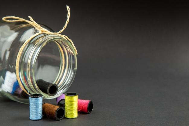 Vista frontal fios coloridos com lata na superfície escura escuridão roupas alfinetes costura medida foto colorida