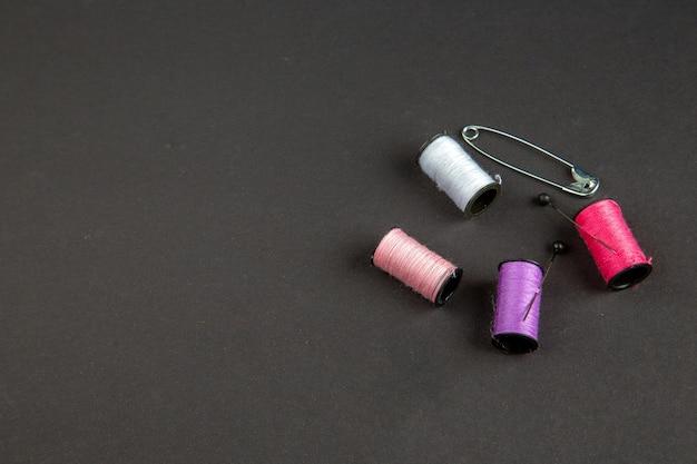 Vista frontal fios coloridos com pino na superfície escura roupas escuras costura mulher costurar pino foto cor tricotar