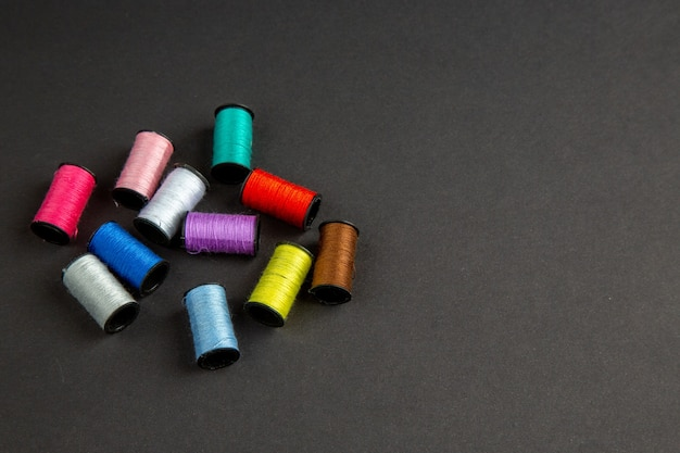 Vista frontal fios coloridos na superfície escura roupas escuras costura foto colorida de malha