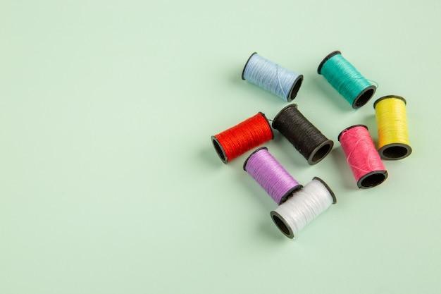 Vista frontal fios coloridos na superfície verde costurando roupas cor de agulha alfinetes de costura