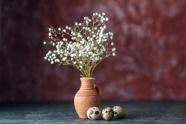 Vista frontal flores brancas com ovos de codorna em fundo escuro beleza galho de árvore foto colorida natureza comida pássaro