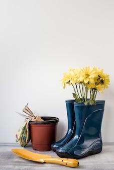 Vista frontal flores em botas e ferramentas de jardinagem