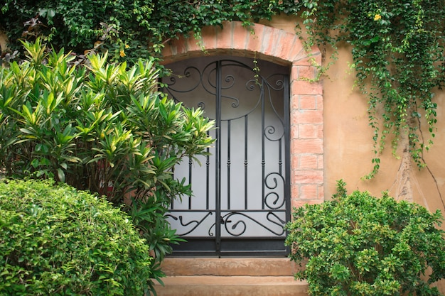 Vista frontal fora da bela casa e porta da frente com árvores.