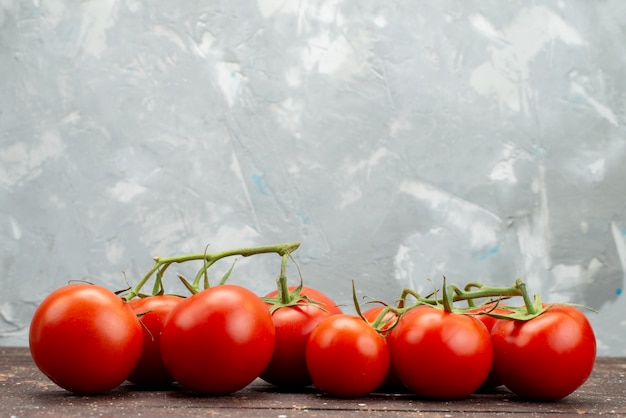 Vista frontal frescos tomates vermelhos maduros e inteiros na madeira, marrom vegetais frutas baga comida cor