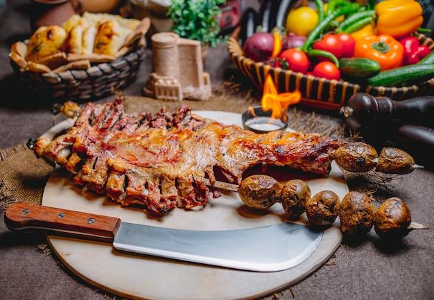 Vista frontal frito costelas de cordeiro em um tandoor no espeto com batatas assadas