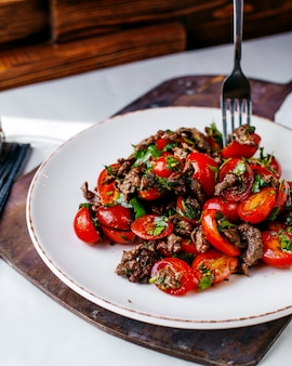 Vista frontal frito legumes carne juntamente com verduras dentro de chapa branca na mesa marrom e backgorund