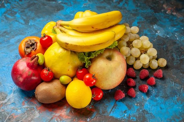 Vista frontal frutas frescas bananas uvas e outras frutas em fundo azul dieta suave cor de saúde madura saborosa