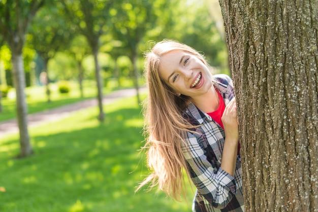 Vista frontal garota feliz posando atrás de uma árvore