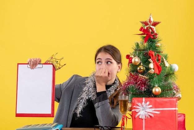 Vista frontal, garota sentada à mesa segurando o documento com a árvore de natal da coroa e coquetel de presentes