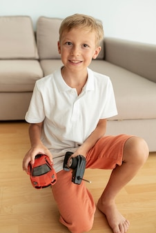 Vista frontal garoto brincando com um carro elétrico