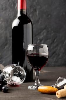 Vista frontal garrafa de vinho tinto e óculos