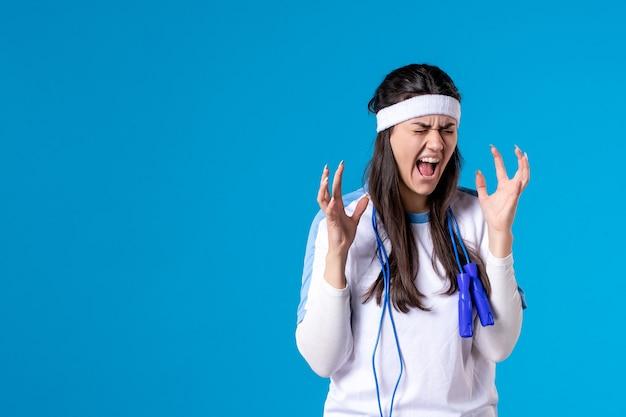 Vista frontal gritando muito feminino em roupas esportivas e pular corda