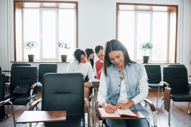 Vista frontal. grupo de pessoas em conferência de negócios em sala de aula moderna durante o dia
