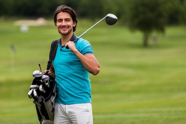 Vista frontal homem adulto com tacos de golfe