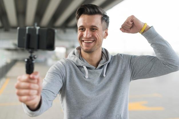 Vista frontal homem adulto tomando uma selfie